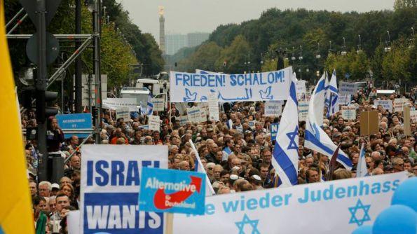 People listen to speakers during anti-Semitism demo at Berlin's Brandenburg Gate
