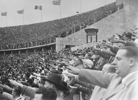 Dans le Stade Olympique, les spectateurs allemands saluent Adolf Hitler lors des 11èmes Jeux Olympiques. Berlin, Allemagne, août 1936.